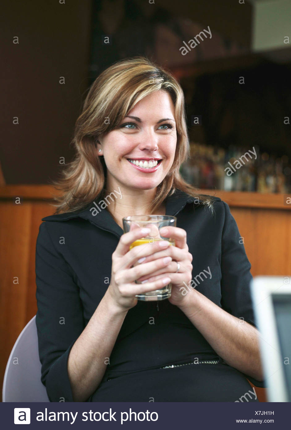 A businesswoman in a meeting in a hotel bar, smiling - Stock Image