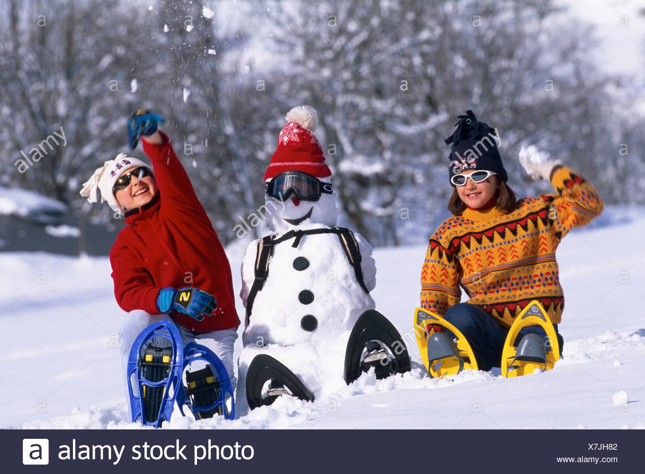 two girls wearing snowshoes, sitting beside a snowman, throwing snow balls. Stock Photo