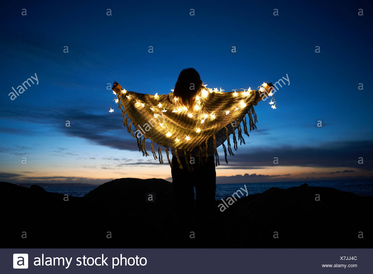 Rear view of woman wrapped in shawl with star fairy lights on beach at night - Stock Image