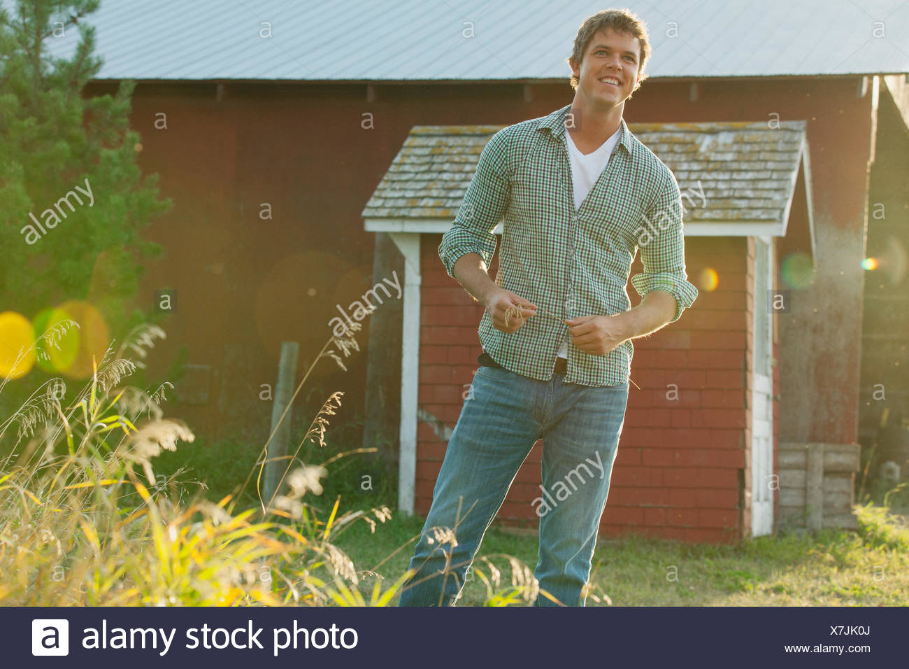 Mid adult man standing by barn on rural property. - Stock Image