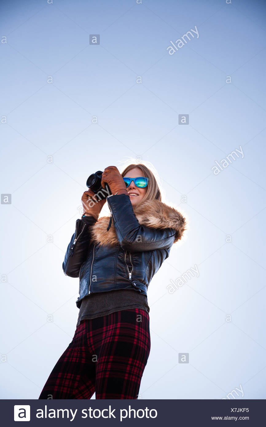 Low angle portrait of woman photographing against blue sky - Stock Image