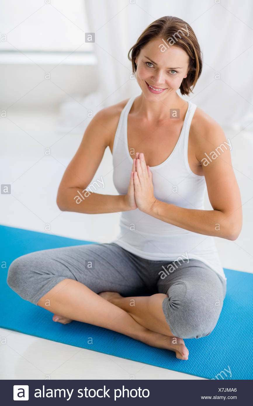Portrait of smiling woman doing yoga - Stock Image