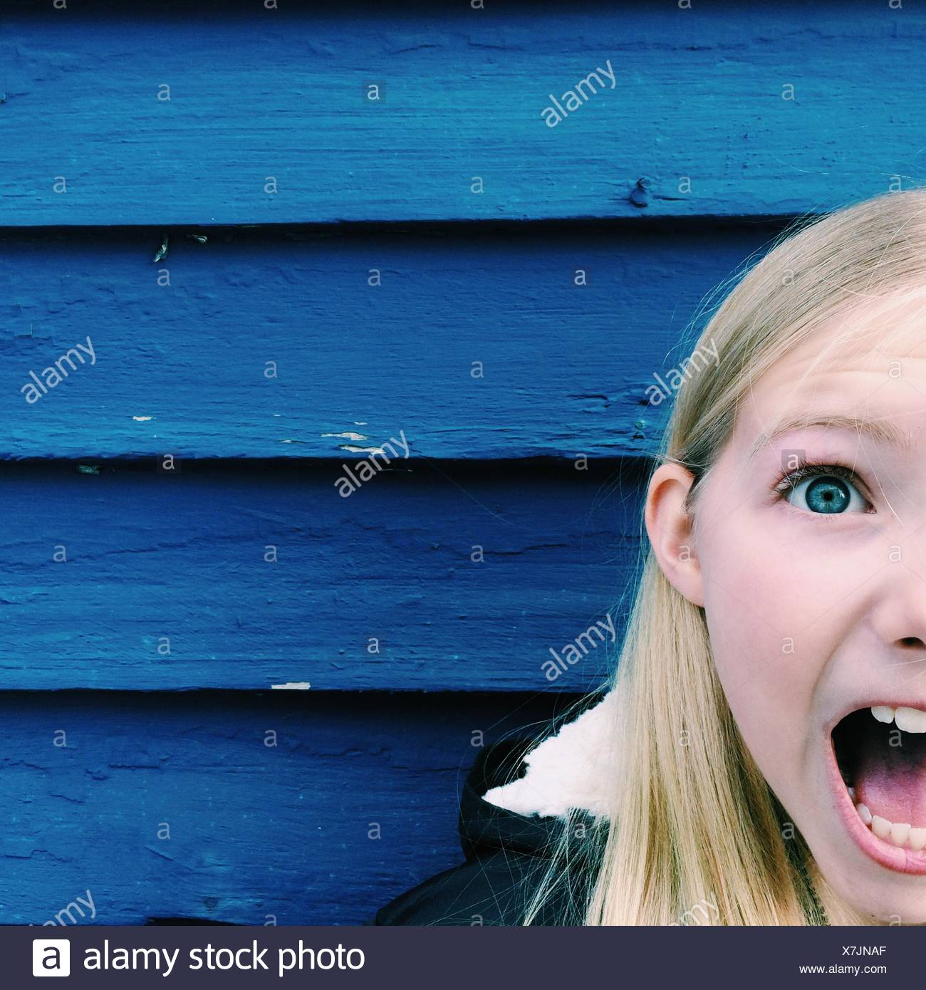 Portrait of a girl with her mouth open shouting - Stock Image
