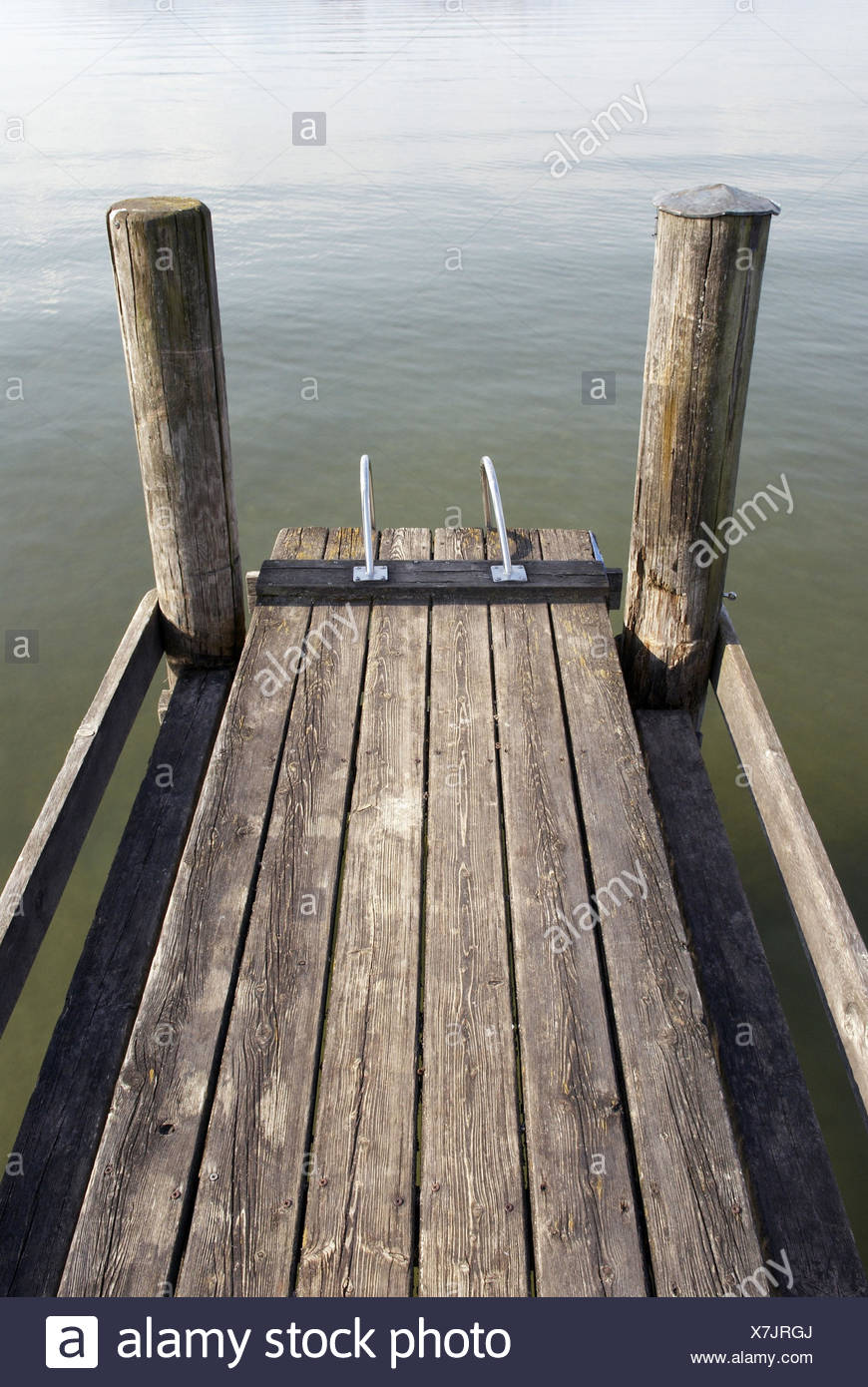 Landing stage, wooden planks, wooden posts, conductors, water, waves, mirroring, - Stock Image