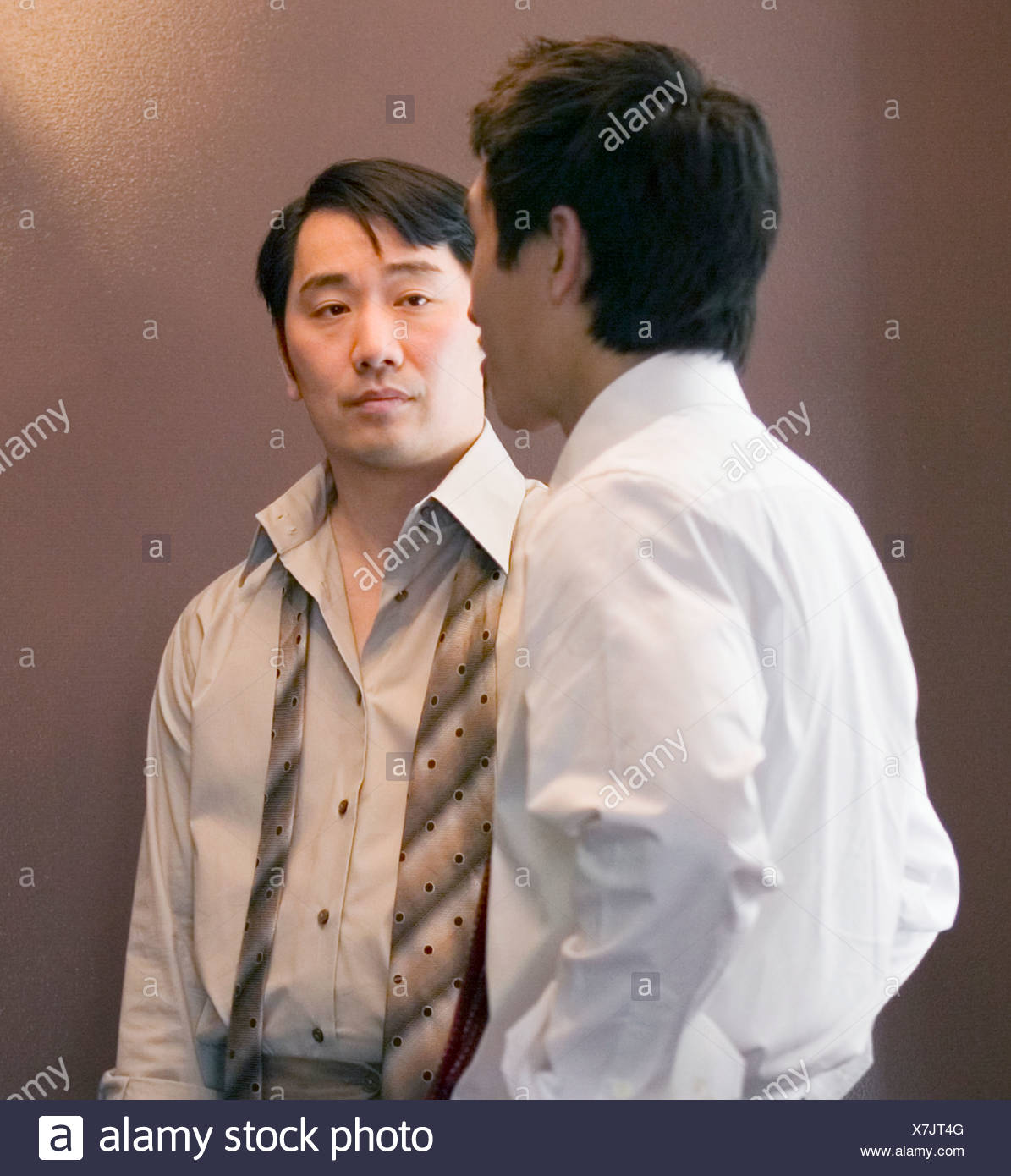 Asian businessman looking at coworker - Stock Image