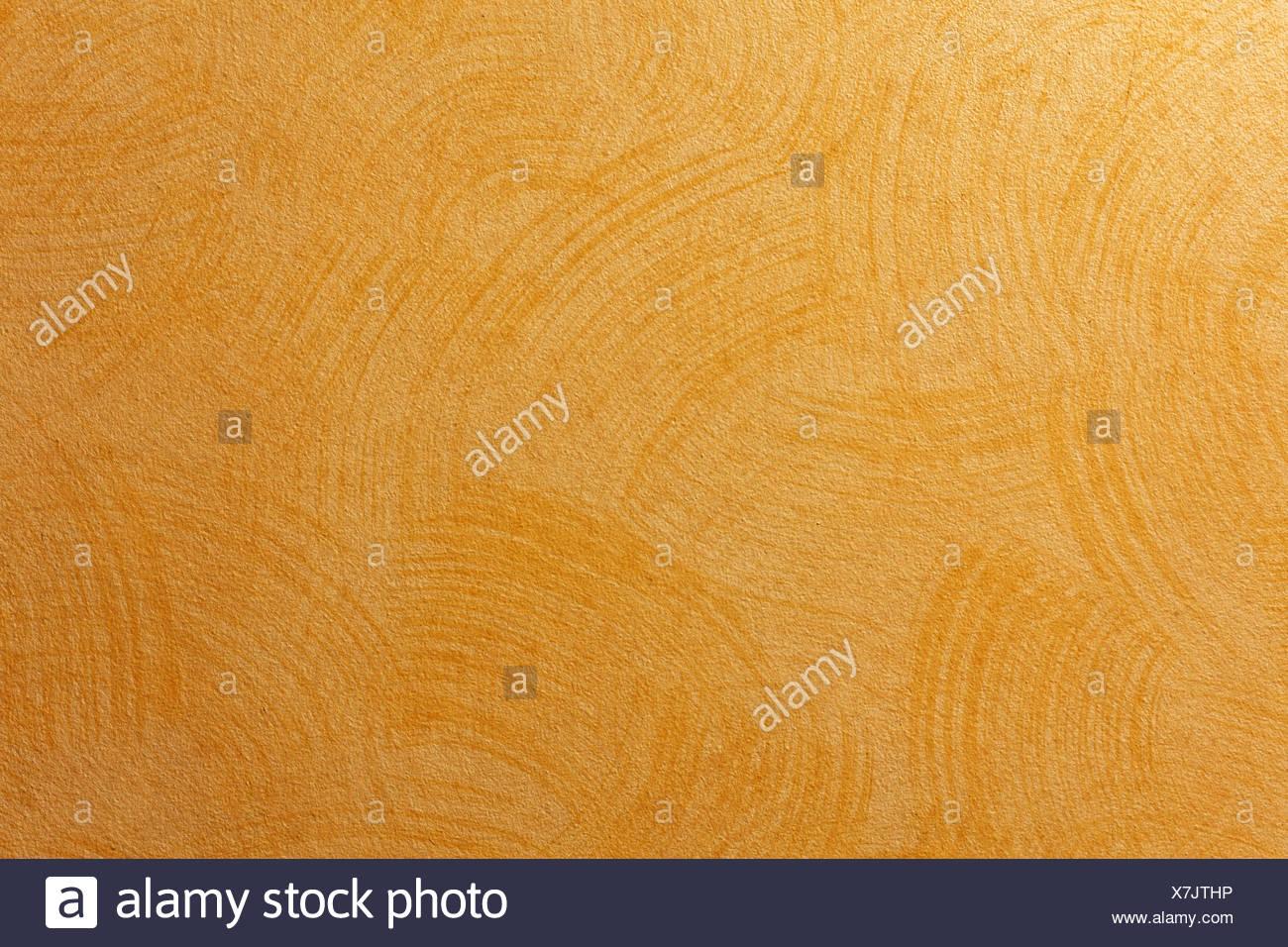Wandgestaltung  mit feinen Zügen einer Bürste auf einer helleren Wand, in Orange. - Stock Image