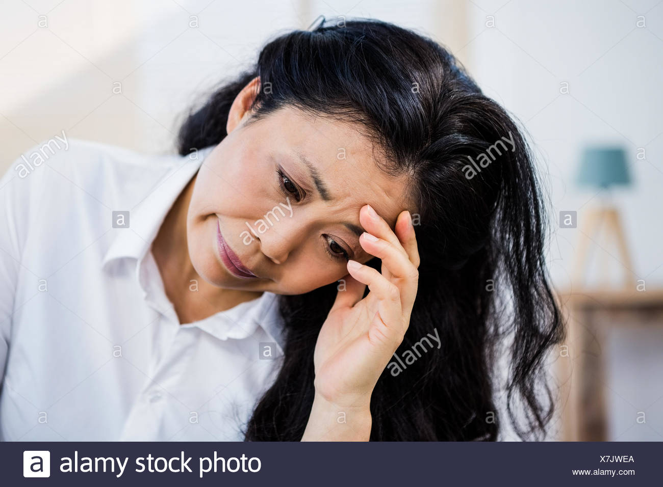 Concerned woman sitting at home - Stock Image