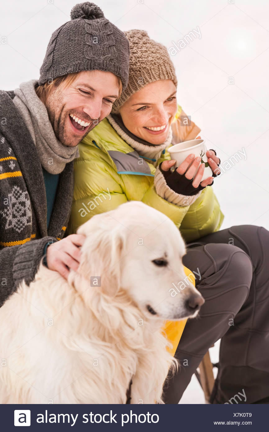 Mid adult couple wearing knit hats with dog Stock Photo