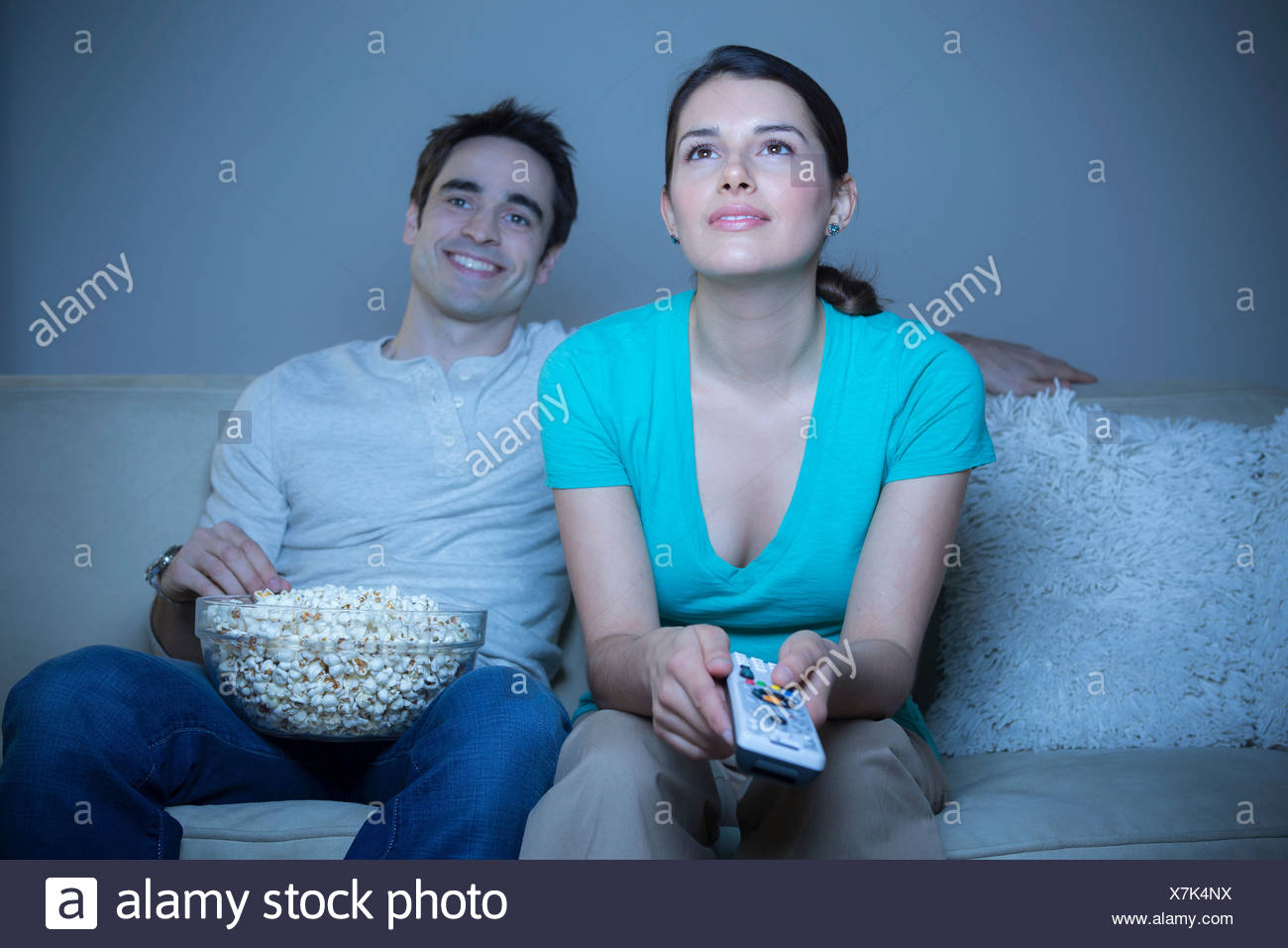 Couple watching television with popcorn - Stock Image