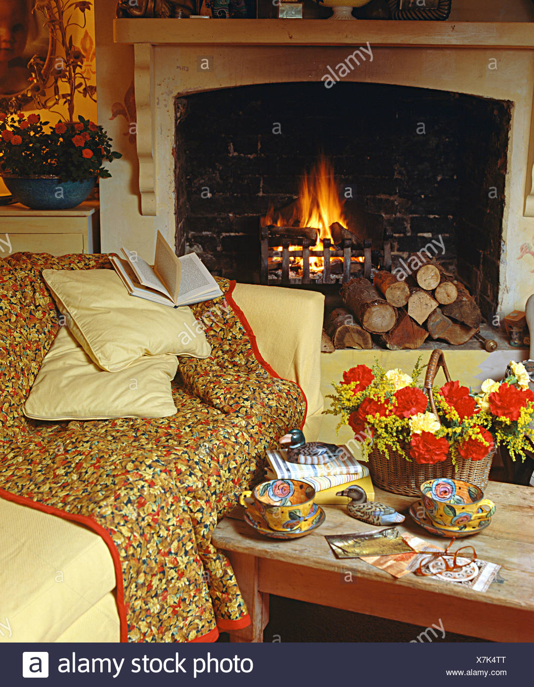 Basket Of Flowers On Small Table Beside Fireplace And Sofa With