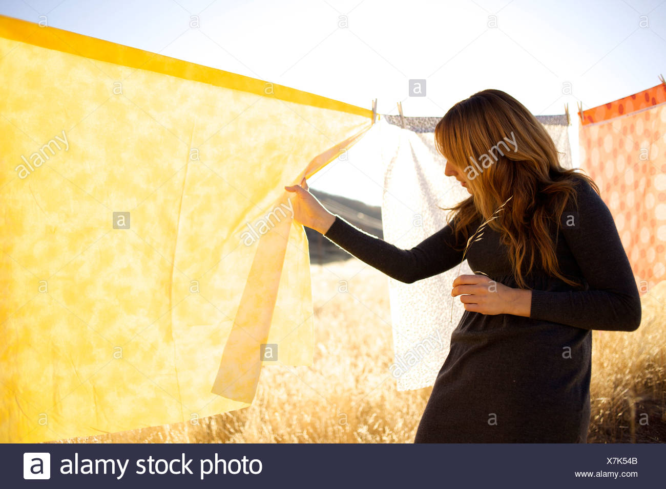 Female moves a yellow sheet hanging on a clothes line to look at what is on the other side. - Stock Image