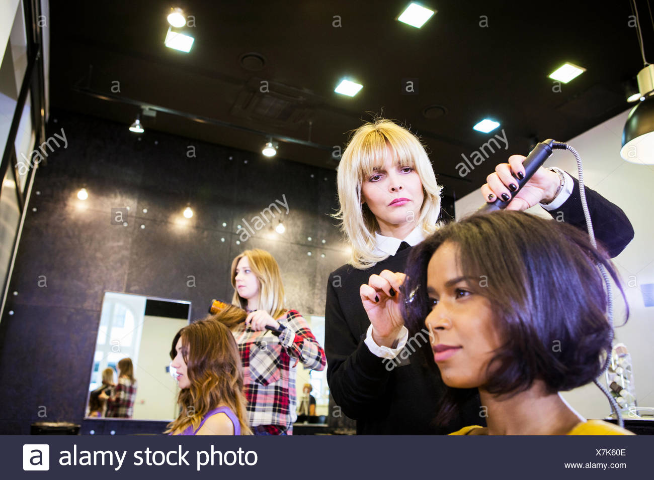 Hairdresser drying customer's hair with hairdryer - Stock Image