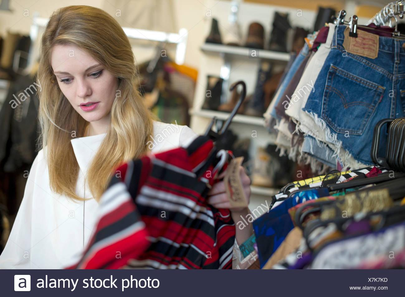 Woman looking at top garment - Stock Image