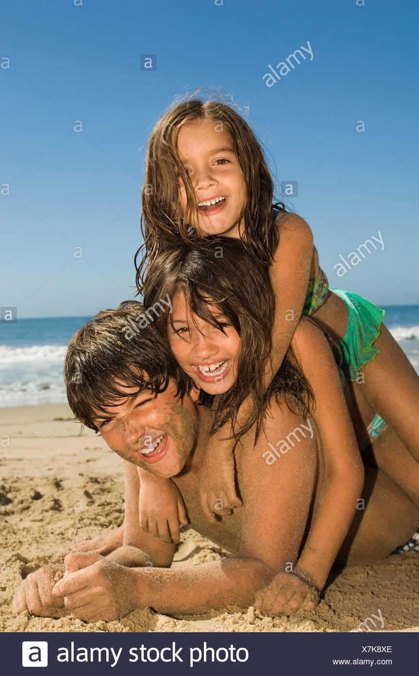 Children in swimwear playing on beach - Stock Image