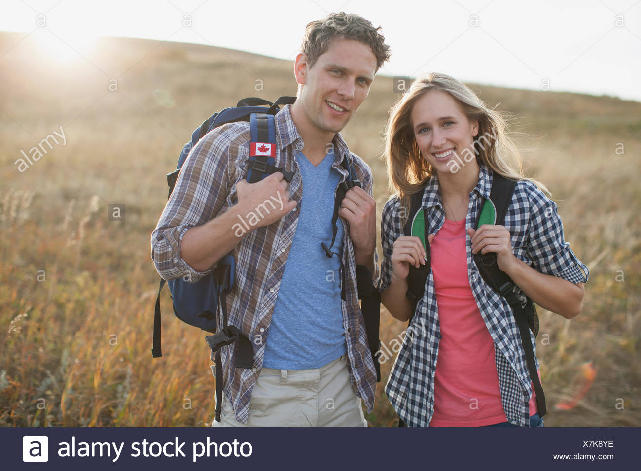 Attractive couple with backpacks in field. - Stock Image
