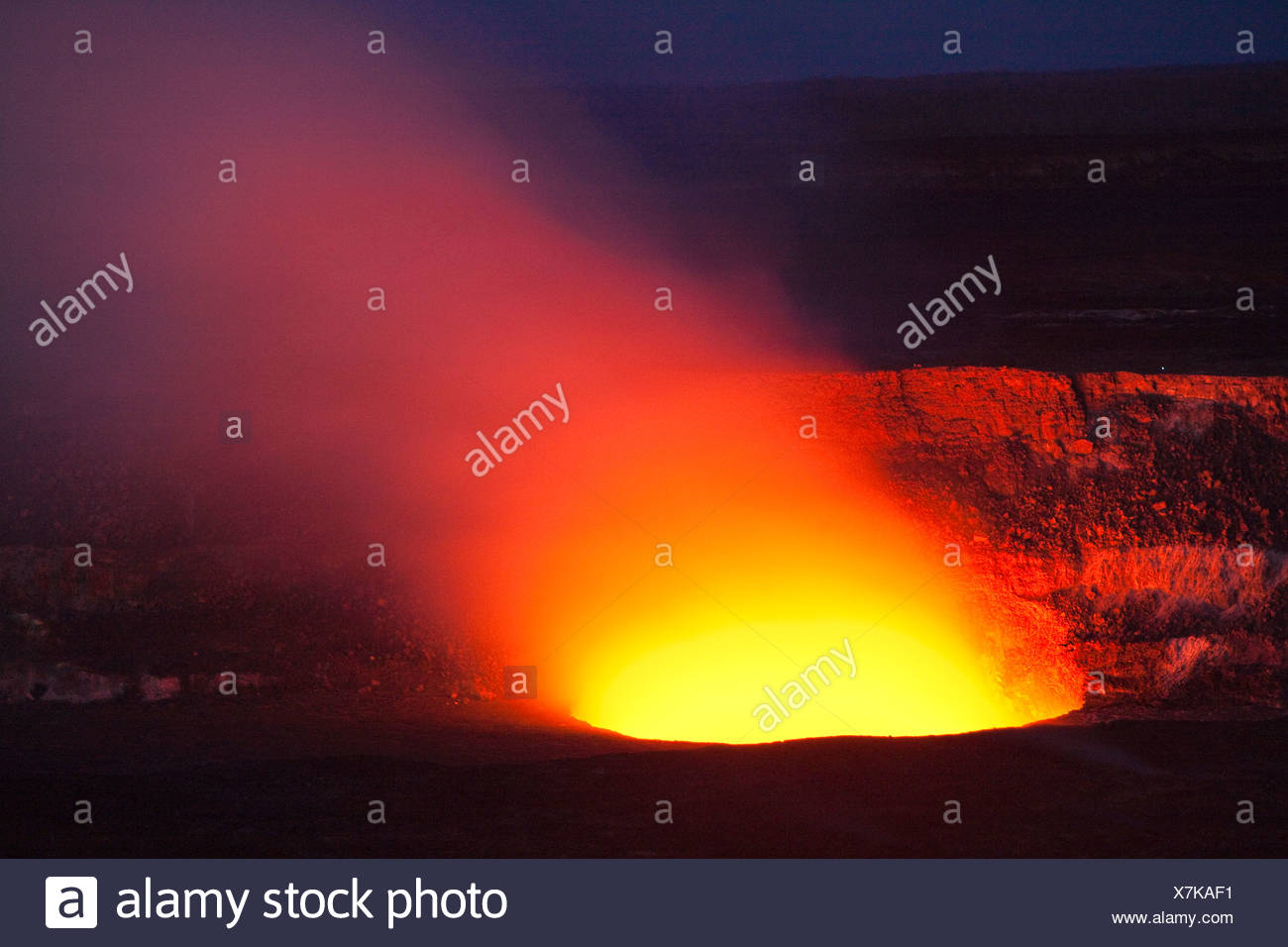 Magma in the Halema'uma'u Crater in the Kilauea Caldera illuminating the rising sulfur dioxide plume against the evening sky - Stock Image