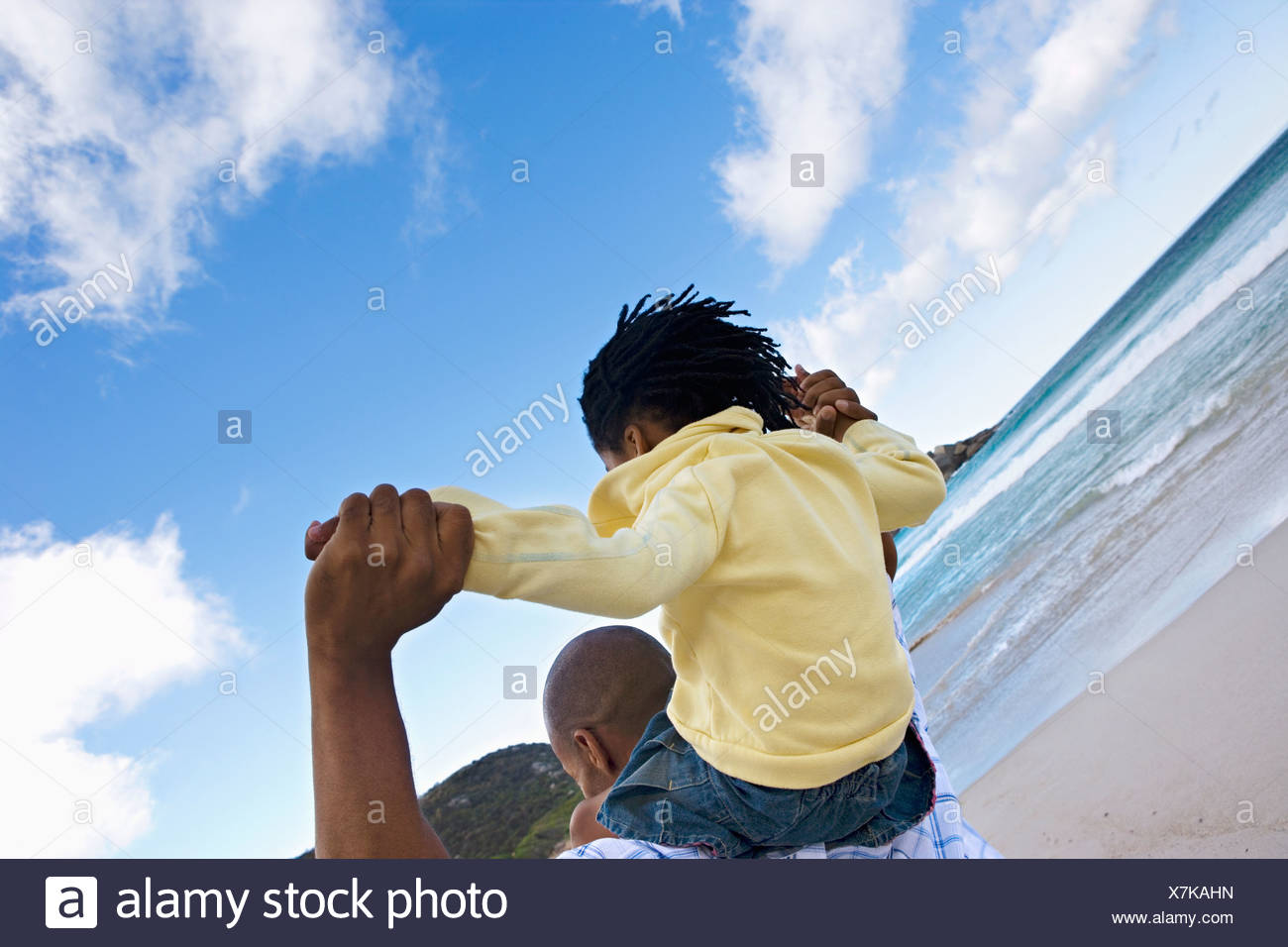 Father carrying daughter 5 7 on shoulders walking on beach smiling rear view tilt Stock Photo