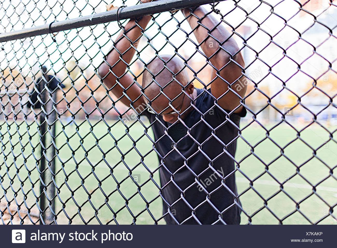 Man behind a chain link fence - Stock Image