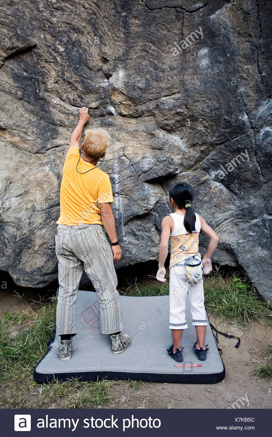 A young climber bouldering with her father in Central Park. - Stock Image