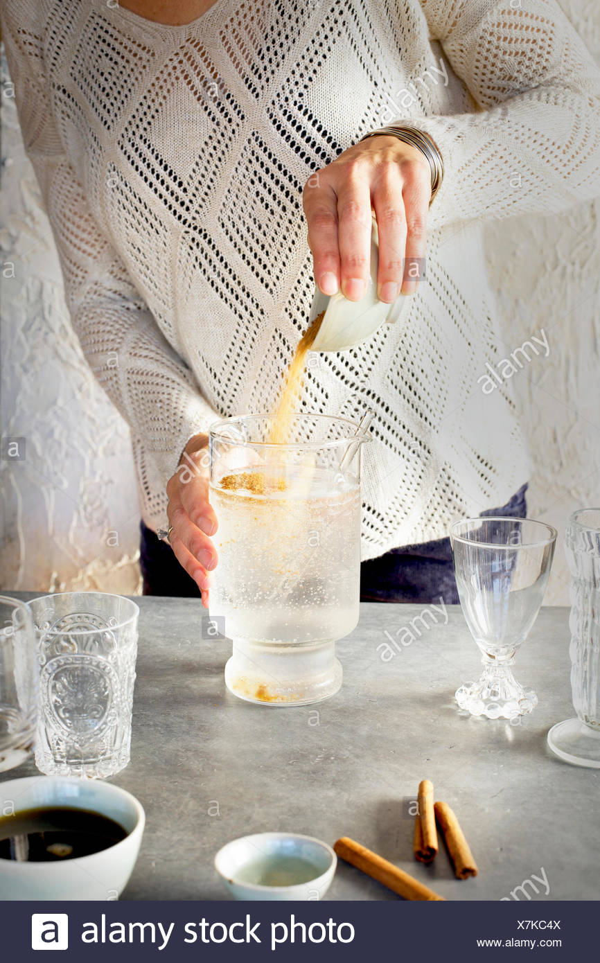 A Women is pouring sugar into Soda Water in glassware. Photographed on dark gray background. - Stock Image