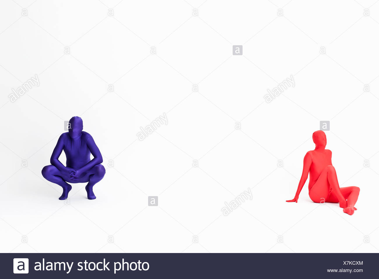 Couple in bodysuits sitting on floor - Stock Image