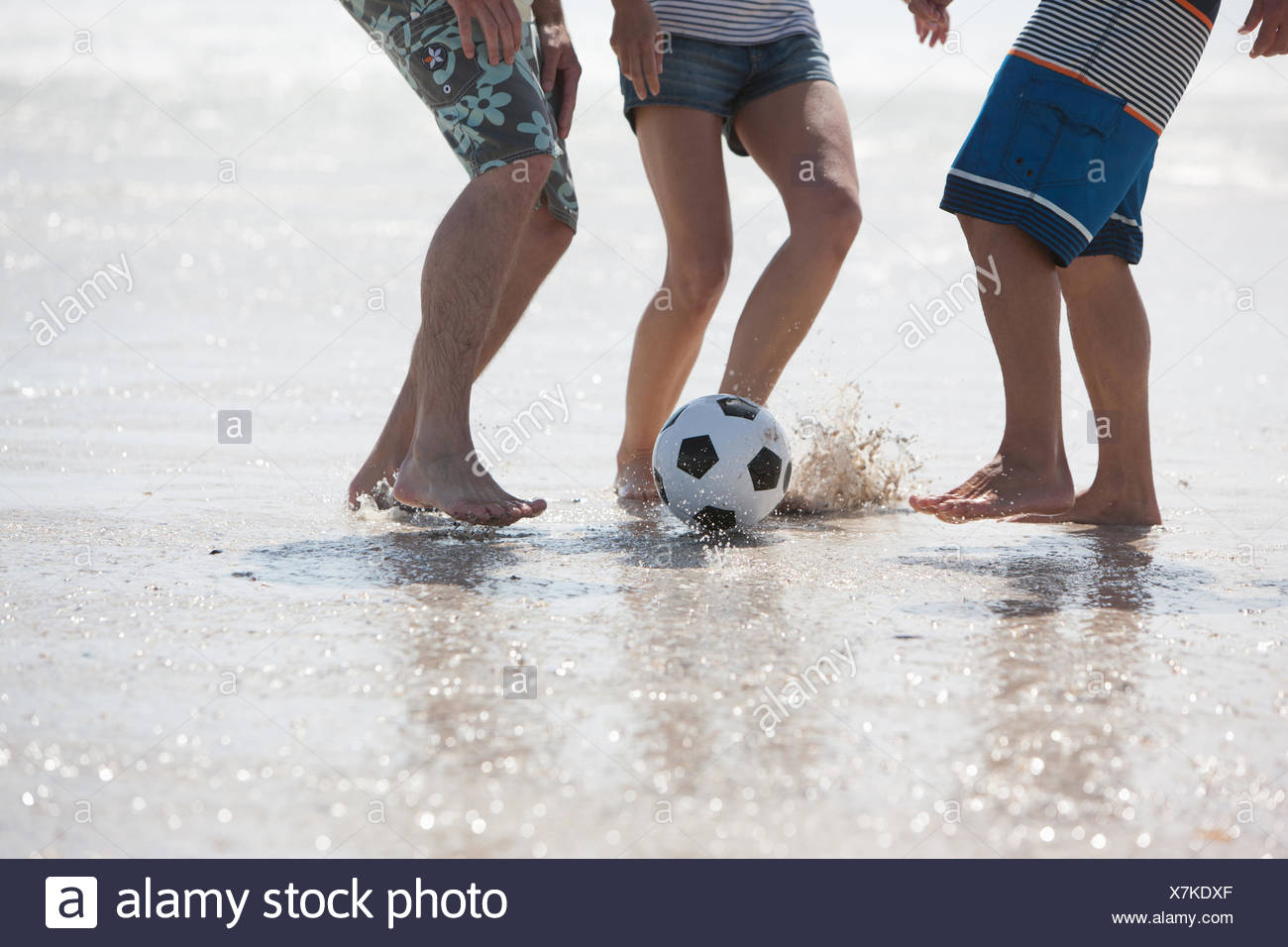 Friends playing football on beach Stock Photo