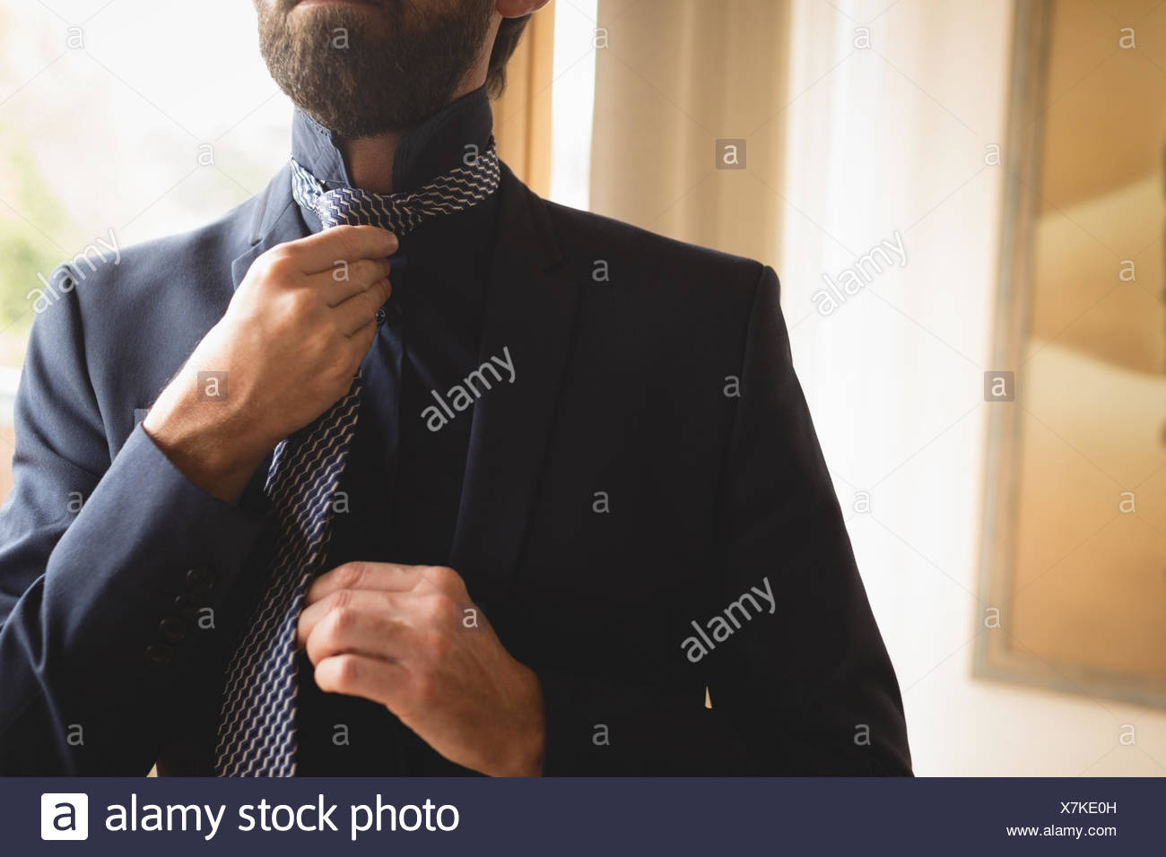 Man wearing his tie at home - Stock Image