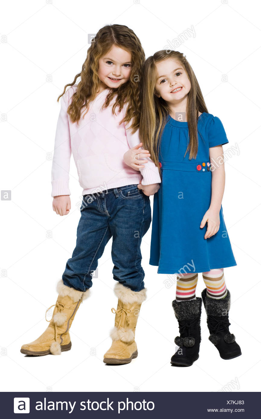 Studio portrait of two girls (4-7) arm in arm - Stock Image
