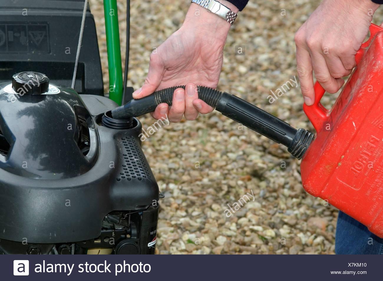Filling petrol tank on petrol driven rotary mower - Stock Image