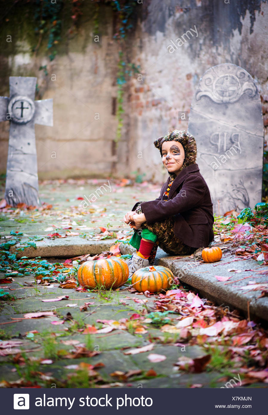 Boy in halloween costume sitting in cemetery - Stock Image