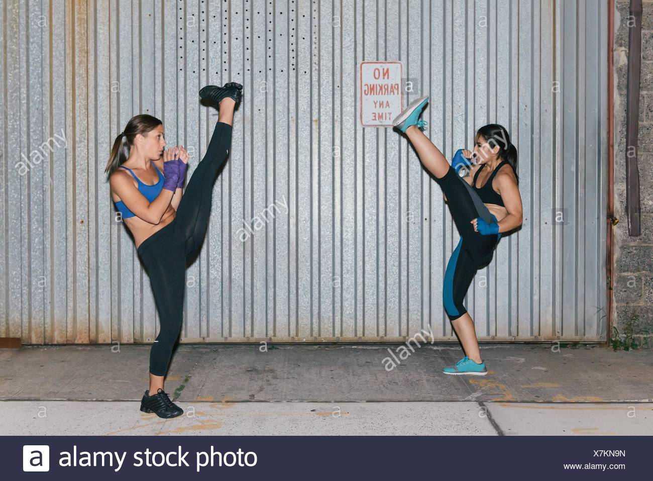 Two female friends exercising and kick boxing towards each other - Stock Image