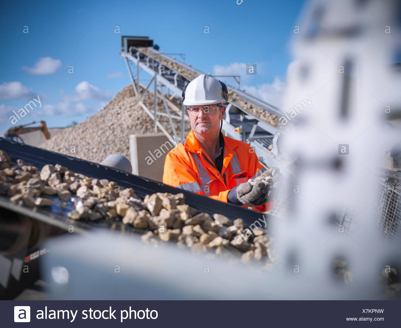 Worker examining stones on conveyor belt - Stock Image