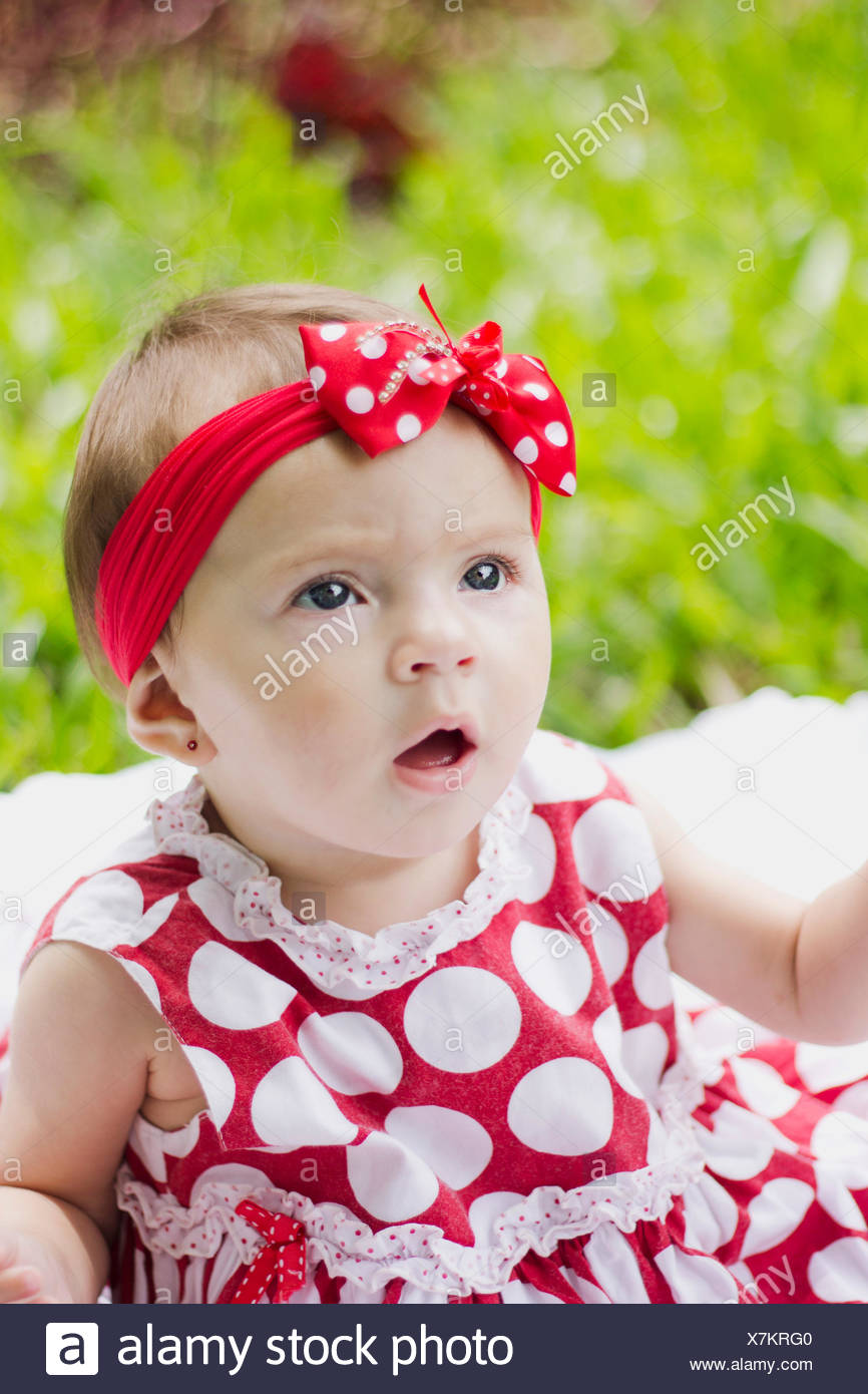 Close-Up Of A Pretty Baby Girl On Grassland - Stock Image