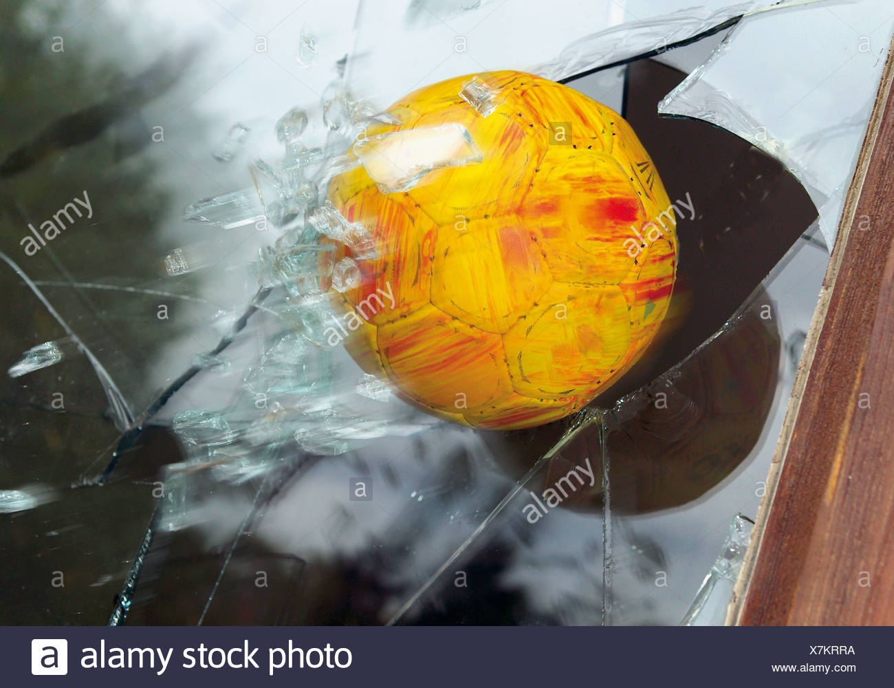 Close up of broken glass window by soccer ball - Stock Image