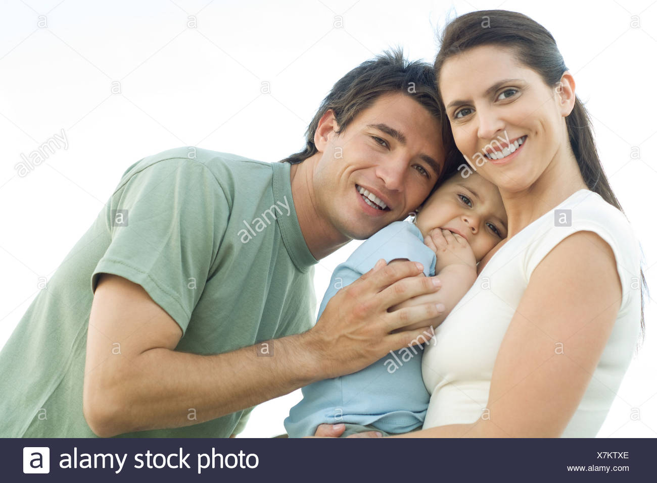 Family smiling at camera, mother holding baby daughter, father leaning in and gently hugging the baby - Stock Image