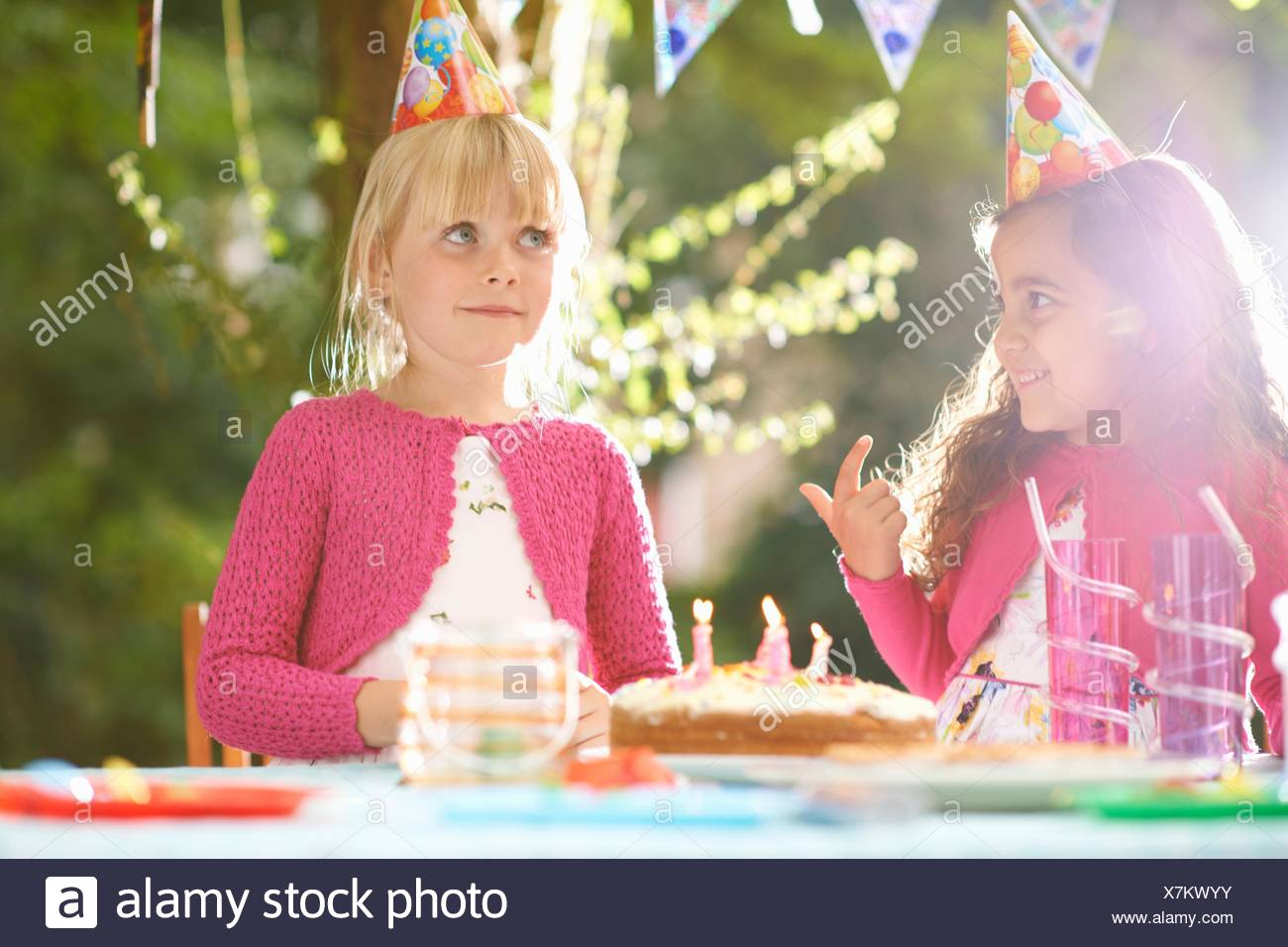 Girls with finger in birthday cake at  garden birthday party - Stock Image