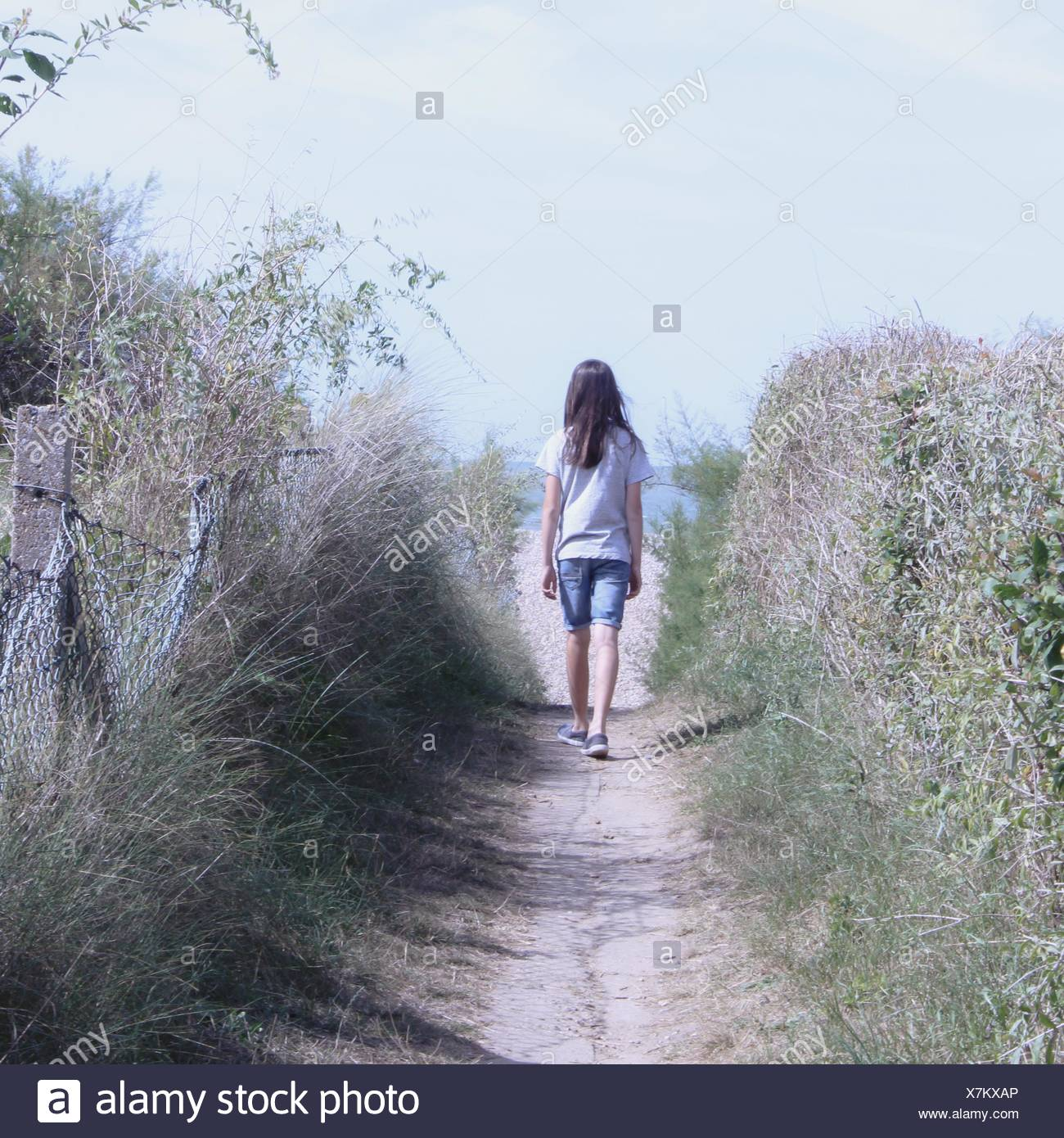 Rear view of girl walking along footpath - Stock Image