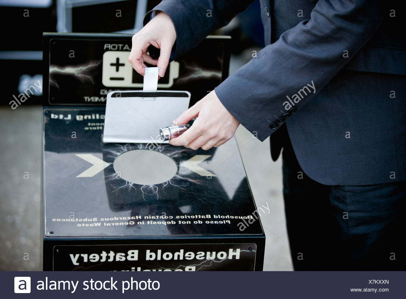 A businessman recycling household batteries - Stock Image