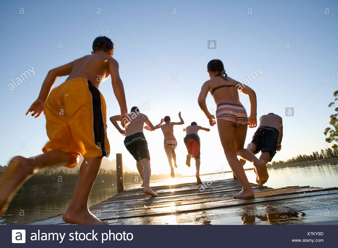 Six family members in swimwear jumping from jetty into lake at sunset rear view lens flare backlit surface level tilt - Stock Image