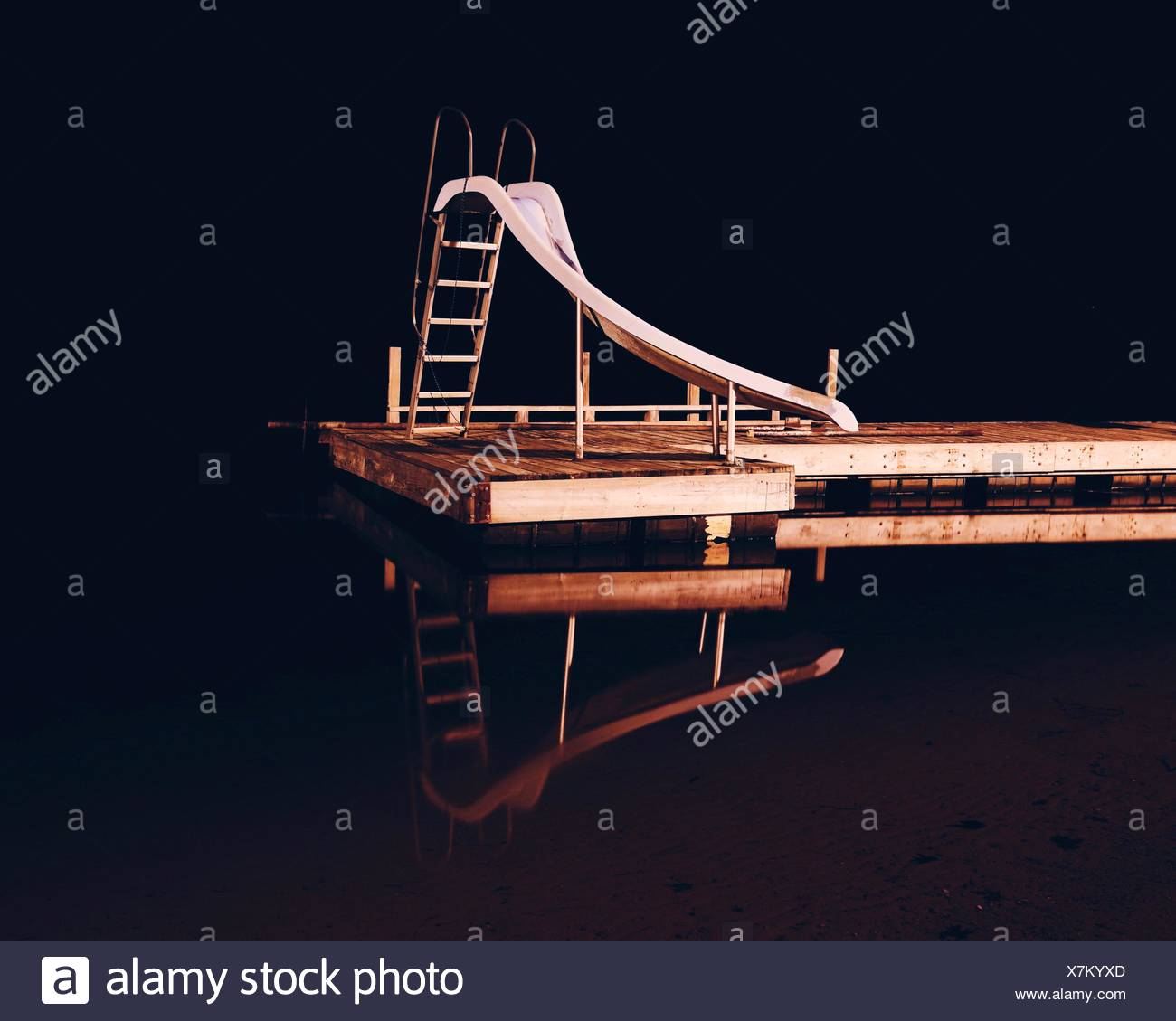Slide By Swimming Pool At Night - Stock Image