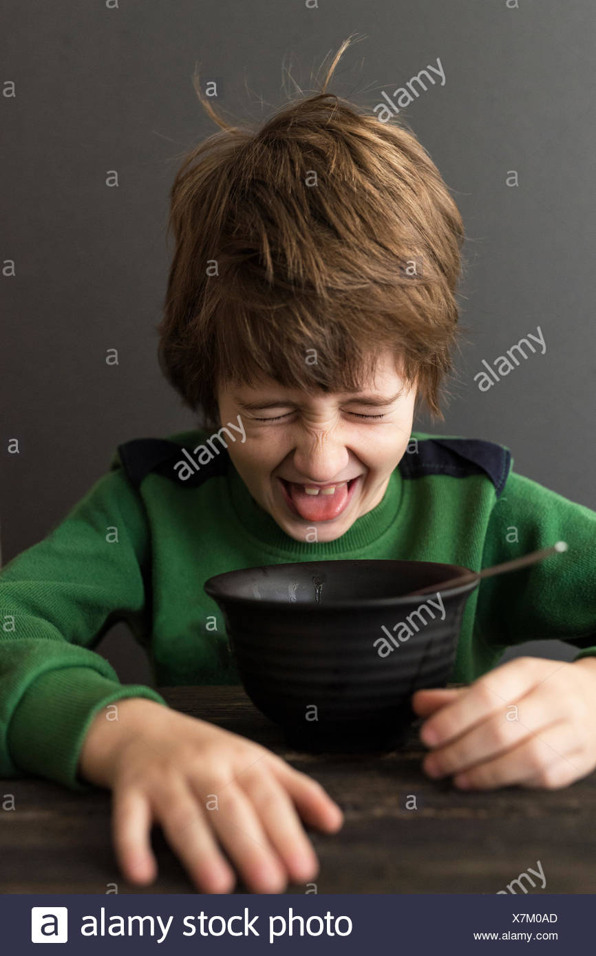 Boy grimacing at a bowl of food - Stock Image