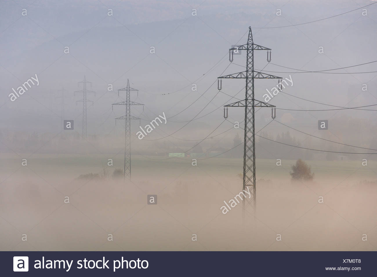 High voltage power line in the morning mist, Berndorf, Triestingtal valley, Lower Austria, Austria, Europe - Stock Image