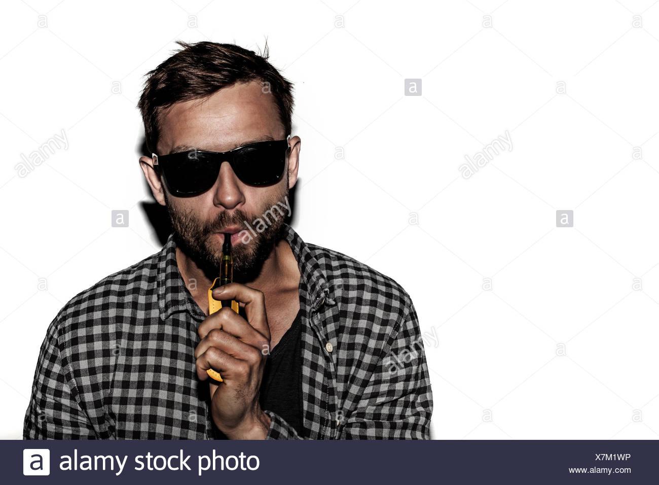 man smoking e-cigarette wearing sunglasses - Stock Image