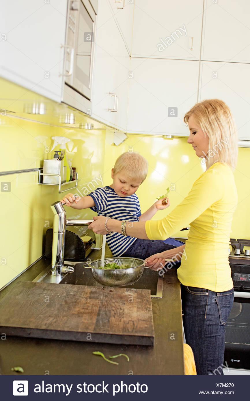 Finland, Helsinki, Kallio, Mother and son in kitchen rinsing lettuce in colander - Stock Image