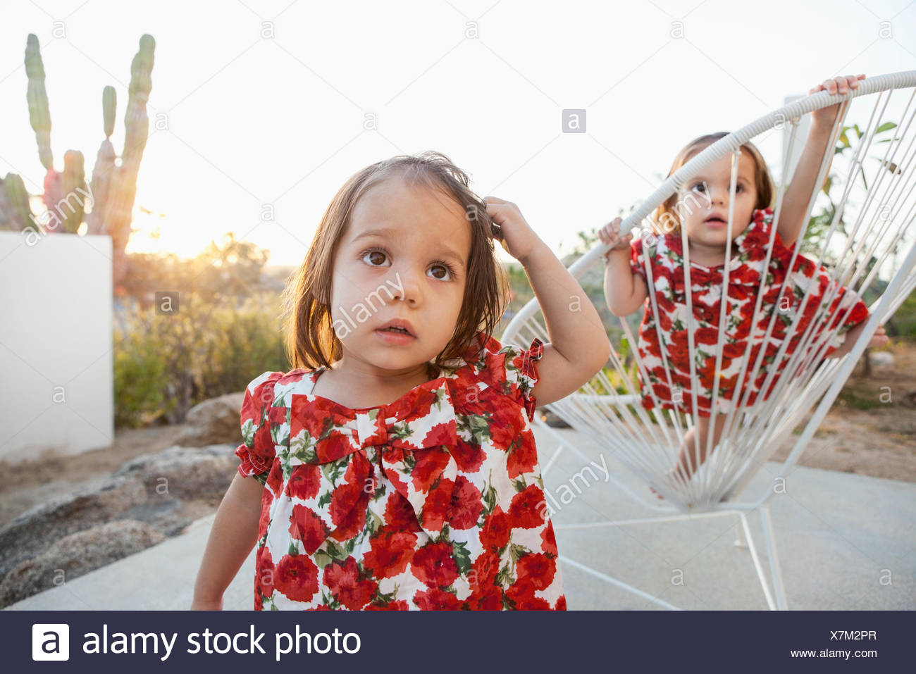 Twin baby girls playing on patio - Stock Image