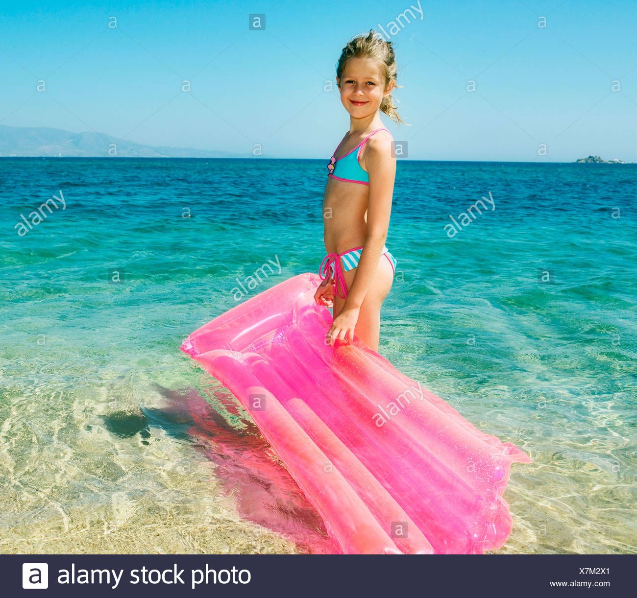 Young girl holding an inflatable raft at the beach smiling. Stock Photo