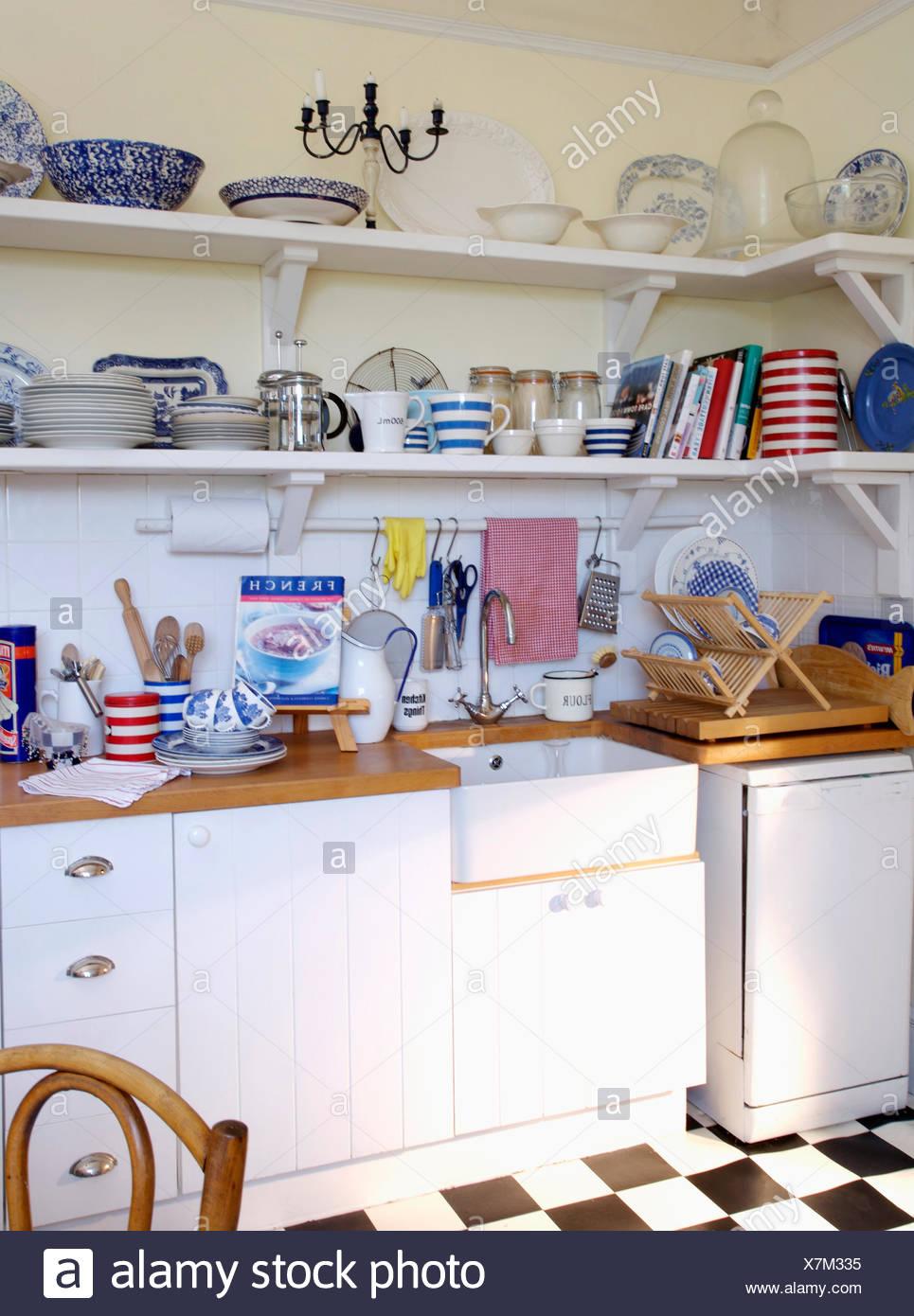 Crockery on shelves above white ceramic sink in white ...