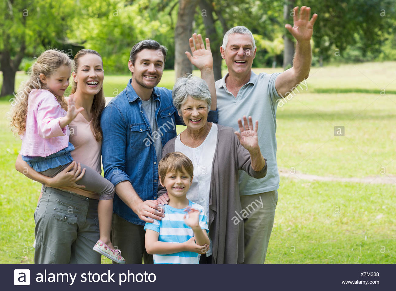Happy extended family waving hands at park - Stock Image