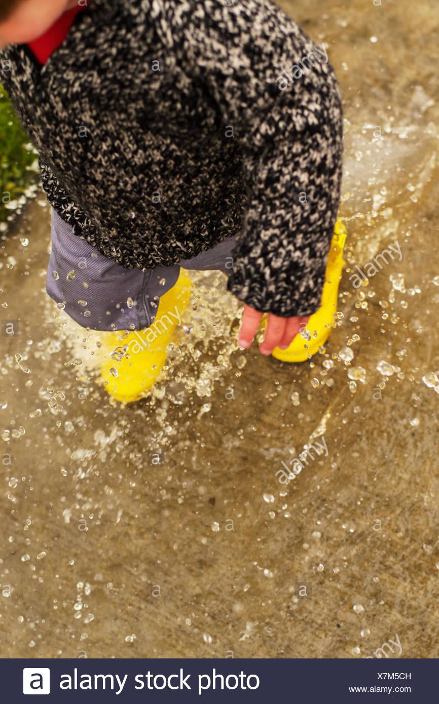 Boy walking through puddle (2-3 years) - Stock Image