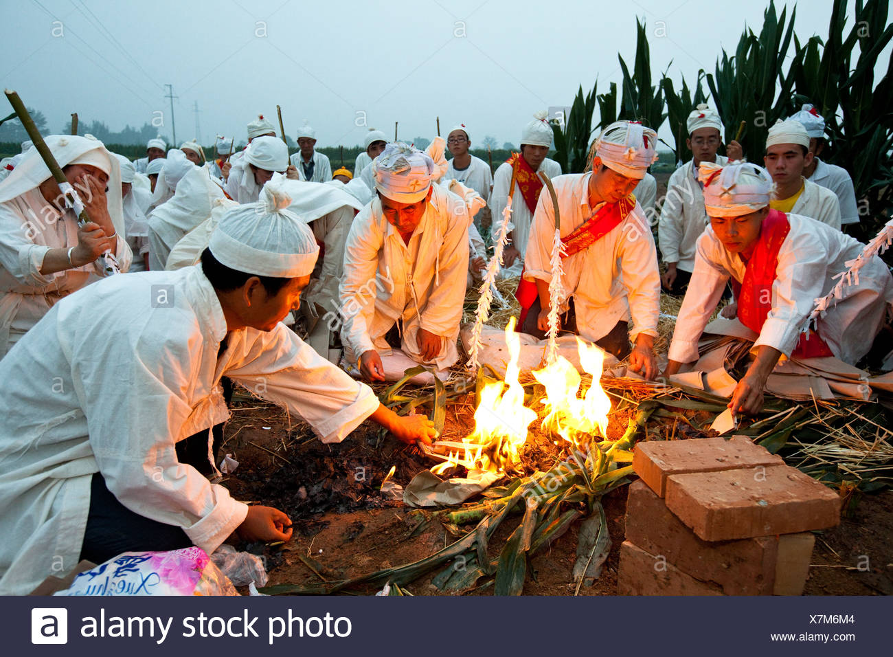 At a grave, relatives observe the ritual burning of paper wreaths. - Stock Image